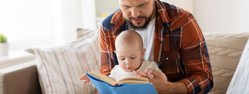 family, parenthood and people concept - happy father and little baby boy with book at home
