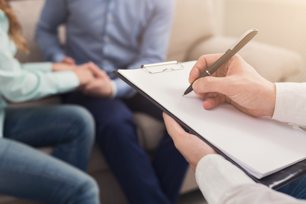 Unrecognizable couple reconciling at therapy session in psychotherapists office, therapist writing in blank notepad, copy space