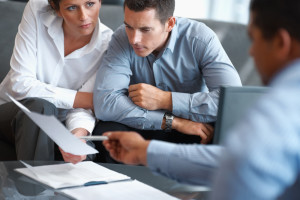 Portrait of a real estate agent consulting a mature couple at office
