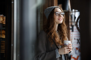 Happy attractive young woman in hat and glasses thinking and drinking coffee outdoors