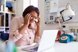 Stressed Mature Woman With Laptop Working In Home Office